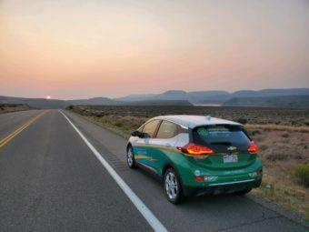 EV driving down road at sunrise